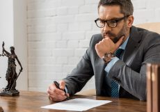 focused male lawyer in eyeglasses working with contract in office