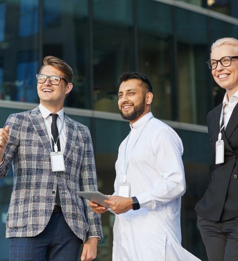 Successful business people looking away and smiling while standing in the city
